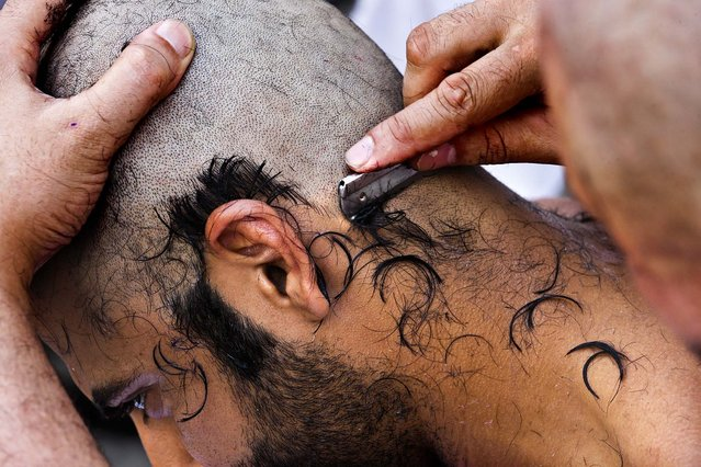 """A pilgrim has his head shaved after he cast stones at a pillar, symbolizing the stoning of Satan, in a ritual called """"Jamarat"""", a rite of the annual hajj, the Islamic faith's most holy pilgrimage, in Mina near the Saudi holy city of  Mecca, Saudi Arabia October 26, 2012. (Photo by Hassan Ammar/Associated Press)"""
