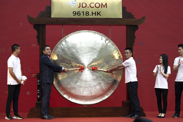 Xu Lei, head of JD Retail, second from left, sounds the gong to mark the listing of JD.com on the Hong Kong Stock Exchange at the JD.com headquarters in Beijing on Thursday, June 18, 2020. Chinese e-commerce firm JD.com's stock jumped nearly 6% on its debut in Hong Kong on Thursday after the firm raised $3.9 billion in a share sale. (Photo by Ng Han Guan/AP Photo)