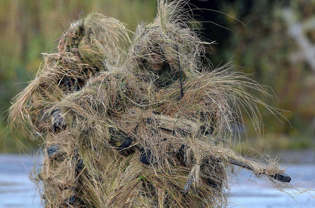 """Looking more like sci-fi creatures, German soldiers are heavily camouflaged in their role as snipers during a military exercise """"Landoperation"""" in Bergen, Germany, 10 October 2014. The German Defense Minister will attend the exercise. (Photo by Peter Steffon/EPA)"""