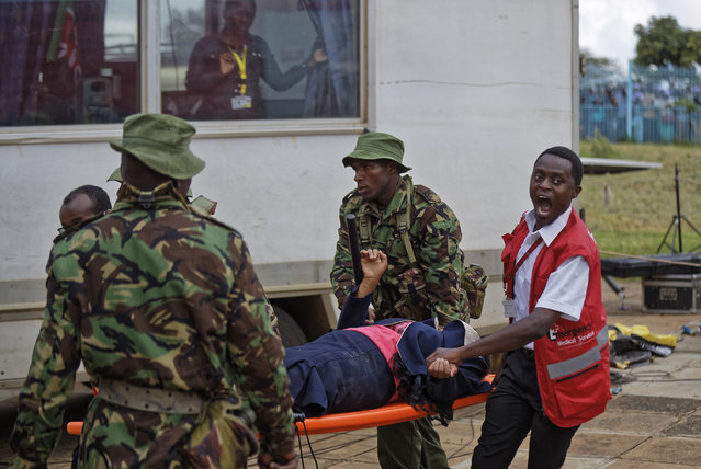 A medical worker shouts out to a colleague as he helps to evacuate a woman injured during clashes between rock-throwing supporters of President Uhuru Kenyatta and police at his inauguration ceremony after they tried to storm through gates to get in and were tear-gassed, at Kasarani stadium in Nairobi, Kenya Tuesday, November 28, 2017. (Photo by Ben Curtis/AP Photo)