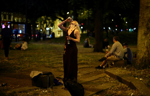 A woman drinks at a bars area in Clapham, after the reopening of commercial activities following the outbreak of the coronavirus disease (COVID-19), in London, Britain, July 4, 2020. (Photo by Hannah McKay/Reuters)