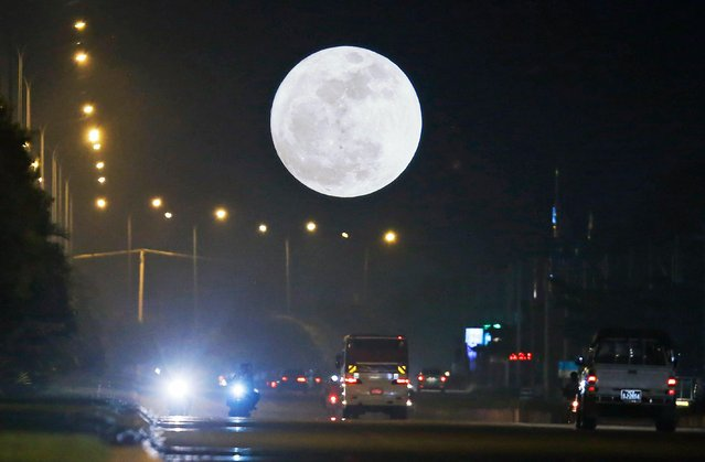 "A so-called ""Supermoon"" dominates the sky while traffic rolls in the streets in Naypyitaw, Myanmar, 03 December 2017. According to the National Aeronautics and Space Administration (NASA) a series of three ""Supermoons"" – dubbed the ""Supermoon trilogy"" – will appear in the sky on 03 December 2017, on 01 January 2018 and and 31 January 2018. A 'Supermoon' commonly is a full moon at its closest distance to the earth with the moon appearing larger than usual. (Photo by Hein Htet/EPA/EFE)"