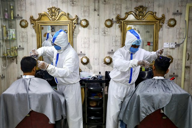 Barbers wearing protective suits and face masks provide hair cut service to the customers inside a salon amid the coronavirus disease (COVID-19) outbreak, in Dhaka, Bangladesh on June 16, 2020. (Photo by Mohammad Ponir Hossain/Reuters)