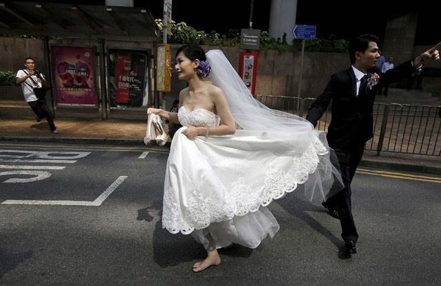 A couple, running late for their wedding ceremony due to the occupation of the main roads by pro-democracy protesters, run towards the marriage registry, in the central business district of Hong Kong Tuesday, October 14, 2014. Hong Kong police removed some barricades on Tuesday from the edge of pro-democracy protest zones that have choked off roads for weeks, the second straight day they have taken such action and signaling their growing impatience with the student-led demonstrators. (Photo by Vincent Yu/AP Photo)