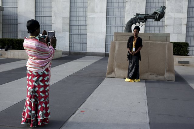 """Women take photo of """"Non Violence"""", a bronze sculpture by Swedish artist Carl Fredrik Reutersward of an oversized Colt Python .357 Magnum revolver, outside the Assembly building during the 70th session of the United Nations General Assembly at the U.N. Headquarters in New York, September 29, 2015. (Photo by Shannon Stapleton/Reuters)"""