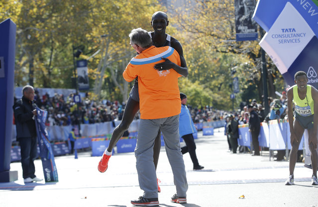 A supporter lifts Wilson Kipsang of Kenya off the ground after he crossed the finish line to win the men's professional division of the 2014 New York City Marathon in Central Park, November 2, 2014. At right is second place finisher Lelisa Desisa of Ethiopia. (Photo by Mike Segar/Reuters)