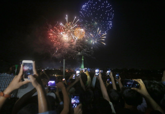 People use their mobile phones to film fireworks close to the Minar-e-Pakistan or Pakistan monument during the Pakistan Independence Day celebrations, in Lahore, Pakistan, Friday, August 14, 2020. Millions of Pakistanis celebrate the 74th Independence Day from British rule. (Photo by K.M. Chaudary/AP Photo)