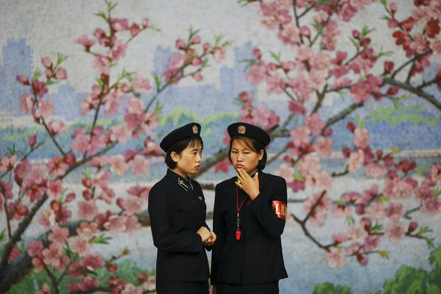 Two railway workers chat in front of a flower mural inside a subway station visited by foreign reporters during a government organised tour in Pyongyang, North Korea October 9, 2015. (Photo by Damir Sagolj/Reuters)