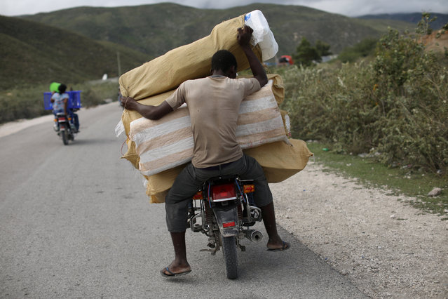 A man holds sacs as he travels in the back of a motorcycle on the way back from the border with the Dominican Republic, in Malpasse, Haiti November 9, 2017. (Photo by Andres Martinez Casares/Reuters)