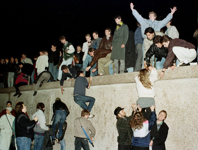 East German citizens climb the Berlin wall at the Brandenburg Gate as they celebrate the opening of the East German border on November 10, 1989. (Photo by Reuters/Stringer)
