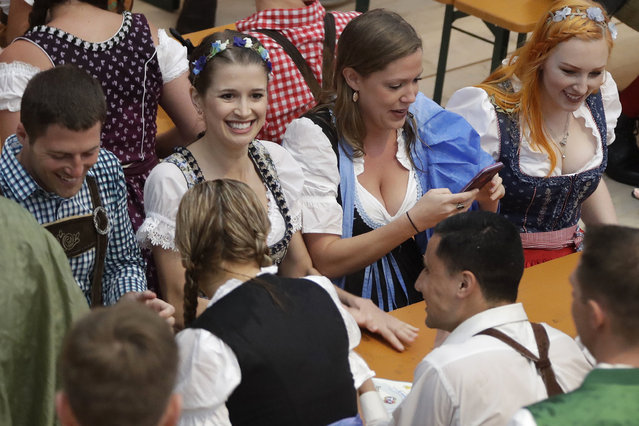 A young woman dressed in traditional clothes smiles after entering a tent prior to the opening of the 183rd Oktoberfest beer festival in Munich, southern Germany, Saturday, September 16, 2016. The world's largest beer festival will be held from Sept. 16 to Oct. 3, 2016. (Photo by Matthias Schrader/AP Photo)