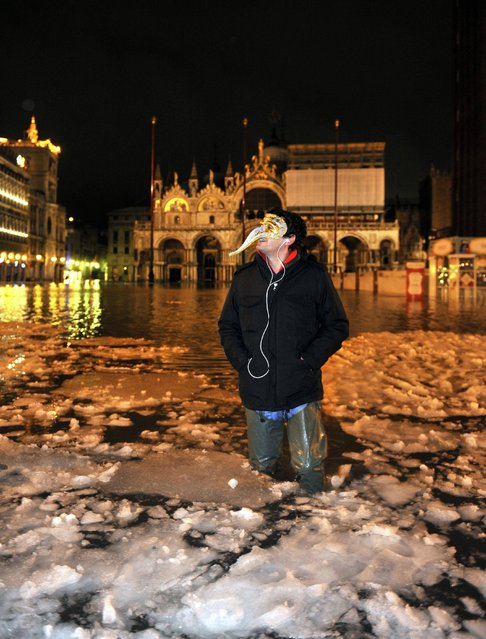 A man wearing a carnival mask wades through high water with floating ice in a flooded St. Mark's Square, in Venice, Italy, early Tuesday, Feb. 12, 2013. The phenomenon of high water, which floods the Venice lagoon, occurs mainly between autumn and spring when tides are reinforced by seasonal winds. The recent snow falls and low temperatures formed ice blocks in the water. (AP Photo/Luigi Costantini)
