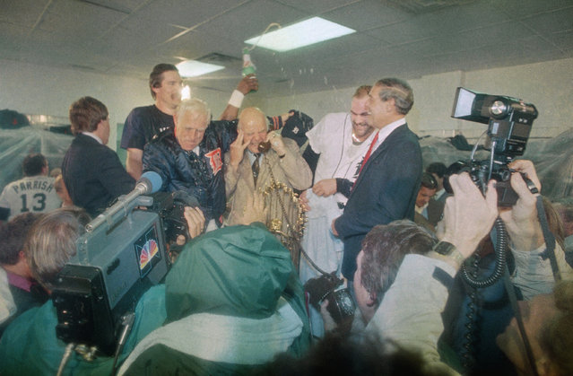 Jim Campbell, President of the Detroit Tigers, center, takes a call from Pres. Ronald Reagan after the Tigers won the World Series, Sunday, October 14, 1984, Detroit, Mich. Pitcher Jack Morris pours champagne over Campbell as manager Sparky Anderson, left, looks on. Others are Kirk Gibson and Bill Lajoie, general manager, right. (Photo by Richard Sheinwald/AP Photo)