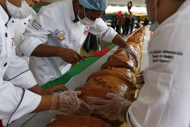 Bakers assemble a giant ham bread, a typical Venezuelan Christmas dish, during an attempt to break the Guinness World Record for the biggest ham bread, in Caracas November 15, 2014. (Photo by Carlos Garcia Rawlins/Reuters)