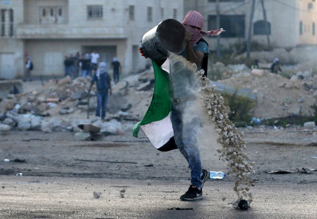 A Palestinian protester drops stones from a bucket to be hurled at Israeli troops during clashes near the Jewish settlement of Beit El, near the West Bank city of Ramallah October 15, 2015. Thirty-two Palestinians and seven Israelis have been killed in the past two weeks of bloodshed. The Palestinian dead include 10 knife-wielding assailants, police said, as well as children and protesters shot in violent demonstrations. (Photo by Mohamad Torokman/Reuters)