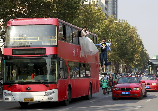 Magician Lei Xin (C) is seen suspended outside a double-deck bus, next to a woman in a wedding gown, as they participate in a performance on a street in Zhengzhou, Henan province, China, October 15, 2015. According to local media, the performance, organized by Lei and his friends, is aiming to promote a healthier view of love and marriage among young people. (Photo by Reuters/Stringer)
