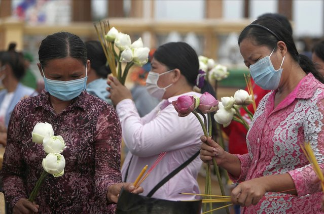 Buddhist followers wearing face masks hold incense sticks and lotus flowers to offer for prayer in front of Royal Palace during Buddhist holidays in Phnom Penh, Cambodia, Friday, September 25, 2020. (Photo by Heng Sinith/AP Photo)
