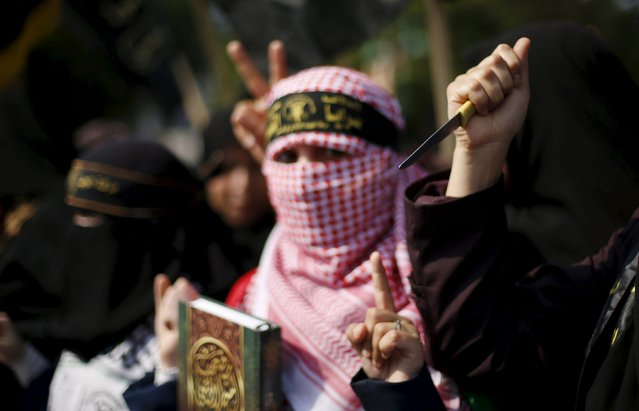 A Palestinian woman supporting the Islamic Jihad movement holds a copy of the Koran as another holds a knife during a rally in Gaza City to show solidarity with Palestinians confronting Israelis in the West Bank and Jerusalem October 20, 2015. (Photo by Mohammed Salem/Reuters)