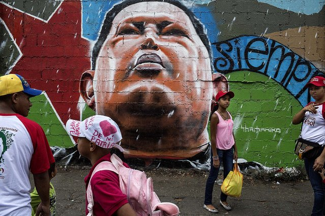 People walk by graffiti showing the late Venezuelan President Hugo Chavez, as they head to pay their final respects during Chavez's funeral ceremony at the military academy in Caracas, on March 11, 2013. (Photo by Mauricio Lima/The New York Times)