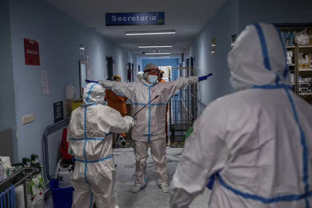 A medical team member is disinfected before leaving the COVID-19 ward at the Severo Ochoa hospital in Leganes, outskirts of Madrid, Spain, Friday, October 9, 2020. At the peak of the first wave, ICU wards were given over to haste, desperation and even cluelessness about what to do. Now, a well-oiled machinery saves some lives and loses others to coronavirus, but without the doomsday atmosphere of March and April. (Photo by Bernat Armangue/AP Photo)