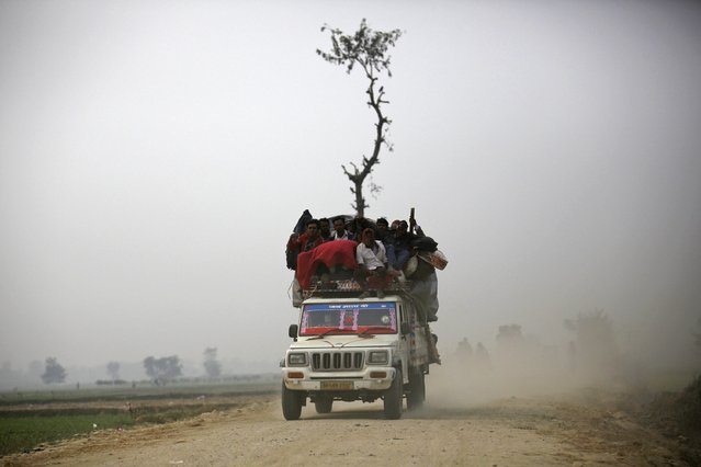 "An overloaded vehicle transports people returning from the ""Gadhimai Mela"" festival held in Bariyapur November 29, 2014. (Photo by Navesh Chitrakar/Reuters)"
