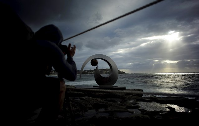 Sunlight peeks through the morning clouds onto the Pacific Ocean as a photographer takes a picture of the stainless steel and bronze sculpture by Australian artist Ben Fasham entitled 'BJF13' during the 19th annual Sculptures by the Sea exhibition in Sydney, October 23, 2015. (Photo by Jason Reed/Reuters)