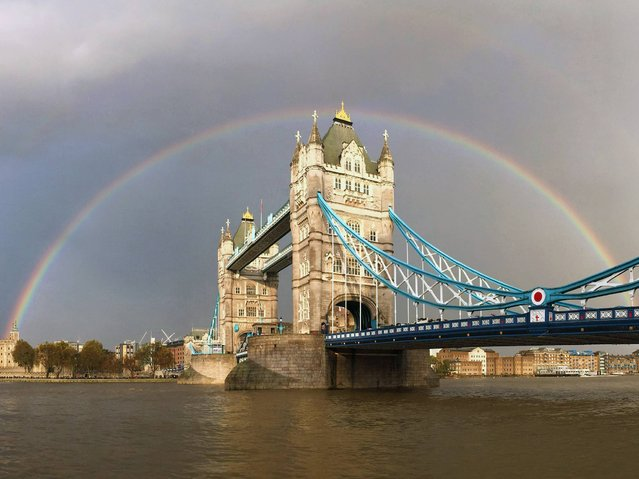 A view of a rainbow behind Tower Bridge in London, on November 1, 2014. (Photo by Paul Gilham/Getty Images)
