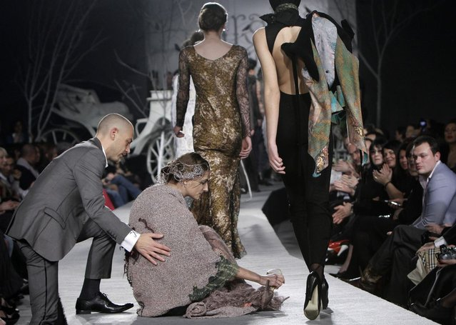 A model is helped by a spectator after she fell while presenting a creation by Georgian designer Irakli Nasidze during Georgian Fashion Week in Tbilisi March 26, 2010. Twenty-one designers and fashion houses participated in the first ever Georgian Fashion Week. (Photo by David Mdzinarishvili/Reuters)