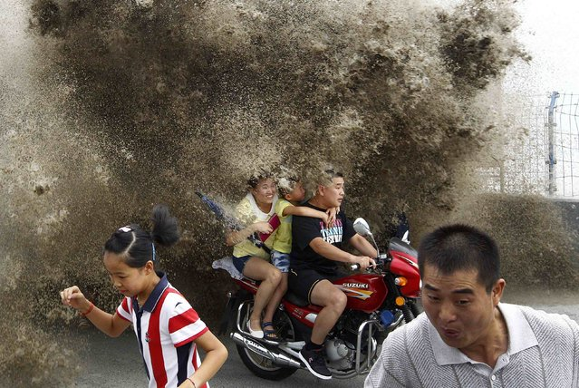 Visitors run away as waves caused by a tidal bore surge past a barrier on the banks of Qiantang River, in Hangzhou, Zhejiang province, in this August 13, 2014 file photo. (Photo by Reuters/Stringer)