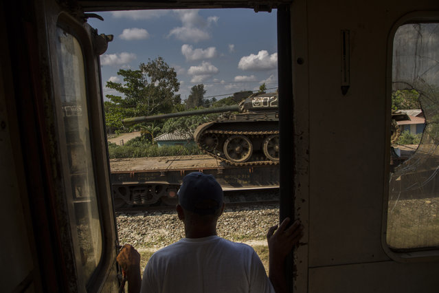 In this March 23, 2015 photo, a man looks at a tank being transported on a paused cargo train, as he travels by train through the province of Holguin, Cuba. The train system suffered along with much of the country's infrastructure when the Soviet Union's collapse cut Cuba off from the subsidies that Moscow had pumped into its economy. Currently, a longstanding U.S. trade embargo makes it hard to get parts. (Photo by Ramon Espinosa/AP Photo)