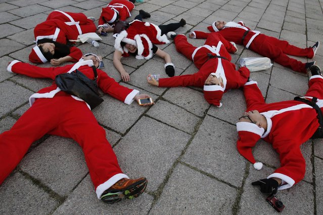 People dressed in Santa costumes rest on the ground after participating in the Tokyo Santa Run at a park in Tokyo December 6, 2014. (Photo by Yuya Shino/Reuters)