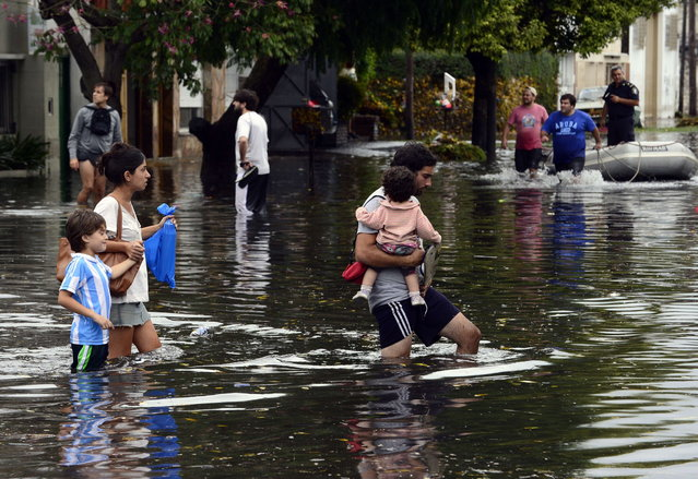 People wade through a flooded streets as the water starts subsiding in La Plata, located 63 km south of Buenos Aires, on April 3, 2013 after a powerful storm that earlier pummeled in the Argentine capital slammed here overnight Tuesday to Wednesday. At least 25 people died in flooding in La Plata as a record 40 cm of rain fell in a two hour period, knocking out phone lines and leaving people in the dark. The deaths raised to 33 the number of people killed this week following record heavy rain in Argentina. (Photo by Daniel Garcia/AFP Photo)