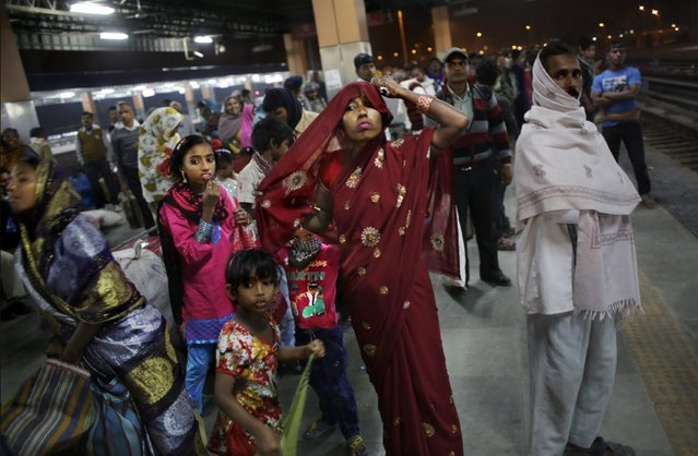 In this November 18, 2014 photo, Marjina adjusts her sari, with her daughter Murshida, 12, and seven-year old son Shahid-ul standing beside as they wait for a train at a railway station in New Delhi, India. (Photo by Altaf Qadri/AP Photo)