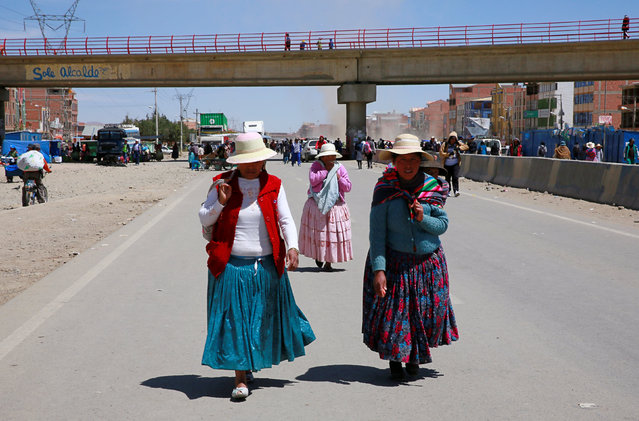 Women walk on a main road blocked by demonstrators who say they are demanding for better infrastructure and development in El Alto, Bolivia, October 5, 2016. (Photo by David Mercado/Reuters)
