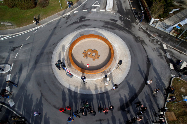 People attend the opening ceremony of world's first public Bitcoin monument, placed at a roundabout connecting two roads at the city centre in Kranj, Slovenia, March 13, 2018. (Photo by Borut Zivulovic/Reuters)