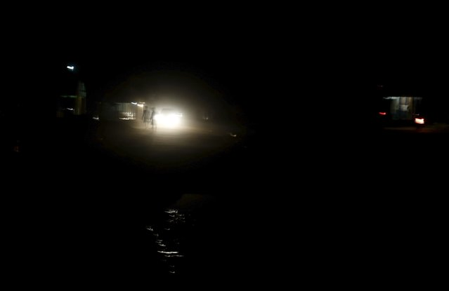 Residents walk on a dirt street illuminated by headlights in Rio Pardo next to Bom Futuro National Forest, in the district of Porto Velho, Rondonia State, Brazil, September 1, 2015. (Photo by Nacho Doce/Reuters)