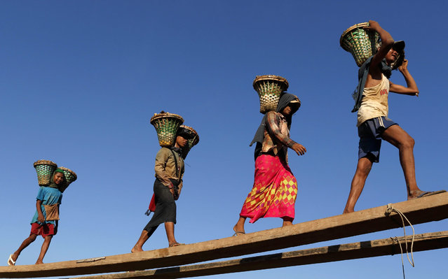 Myanmar laborers and a child laborer (L) carry baskets loaded with gravel used for construction on their shoulders as they unload from a boat at a jetty in Yangon, Myanmar, 06 November 2015. (Photo by Rungroj Yongrit/EPA)