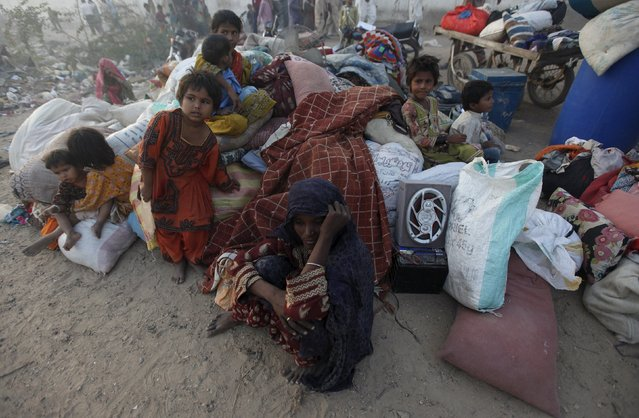 A woman and children sit with their belongings after a fire broke out in makeshift huts in Karachi, Pakistan, October 29, 2015. According to local media, at least five people were killed and several injured after a fire engulfed makeshift huts in Karachi's Gulistan-e-Jauhar neighborhood on Thursday. (Photo by Akhtar Soomro/Reuters)