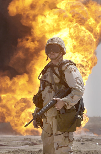 An unidentified US soldier stands guard as oil workers put out an oil well fire at Rumailah oil field, southern Iraq on Tuesday, April 1, 2003. Kuwaiti and American firefighters are putting out the blazes at six oil wells that were sabotaged, reportedly by retreating Iraqi forces. (Photo by Gustavo Ferrari/AP Photo)