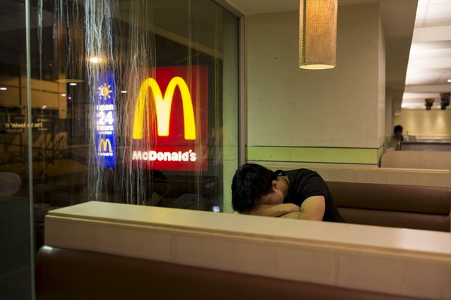A man sleeps at a 24-hour McDonald's restaurant in Hong Kong, China November 10, 2015. (Photo by Tyrone Siu/Reuters)