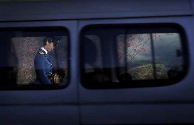 A North Korean traffic police woman is framed by a window of a passing vehicle as she walks past commuters waiting at a bus stop at the end of a workday on Monday, October 17, 2016, in Pyongyang, North Korea. (Photo by Wong Maye-E/AP Photo)