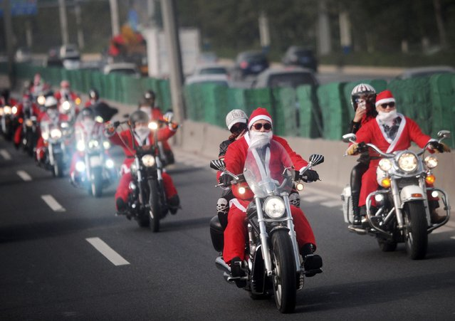 Owners of Harley-Davidson motorcycles wearing Santa Claus costumes ride along a street to give presents to elders at a nursing home during a promotional event celebrating Christmas in Guangzhou, Guangdong province December 24, 2014. (Photo by Reuters/Stringer)