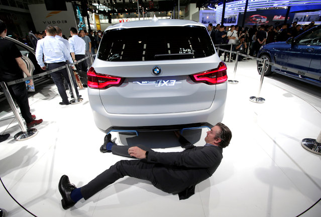 A man checks the BMW iX3 electric concept car during a media preview at the Auto China 2018 motor show in Beijing, China April 25, 2018. (Photo by Jason Lee/Reuters)