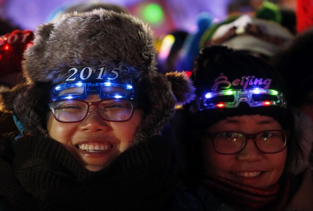"Women wear eyewear in the shape of the year 2015 as they wait for a countdown event to celebrate the arrival of the new year and in wishing winning the bid to host the 2022 Winter Olympic Games, in front of the National Stadium, also known as the ""Bird's Nest"", in Beijing December 31, 2014. (Photo by Kim Kyung-Hoon/Reuters)"