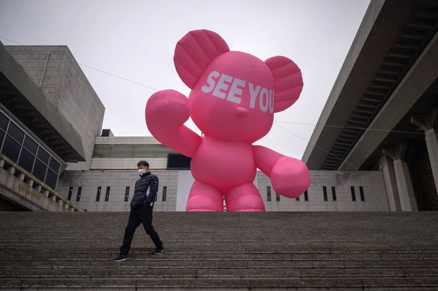 A man wearing a face mask walks down steps before an inflatable bear outside the Sejong theatre in central Seoul on December 10, 2020. (Photo by Ed Jones/AFP Photo)