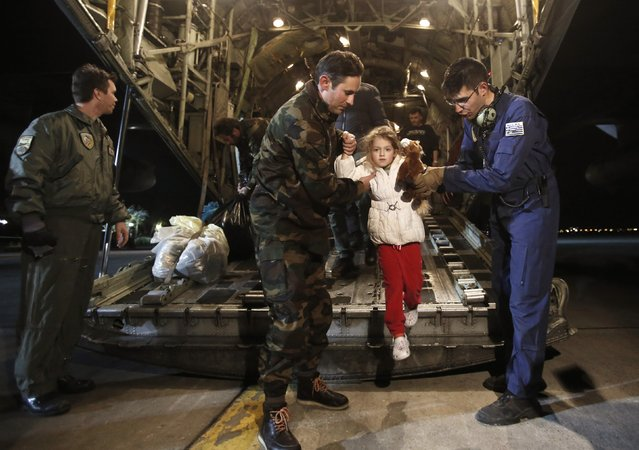 A man (C) and his daughter (2nd L), both rescued from the Norman Atlantic ferry, disembark from a Greek Airforce C-130 military cargo aircraft at the Elefsina military airport near Athens December 29, 2014. Rescue teams evacuated more than 400 people from a car ferry that caught fire off Greece's Adriatic coast in a 36-hour operation on roiling seas, but 10 people were killed in the disaster. (Photo by Yannis Kolesidis/Reuters)