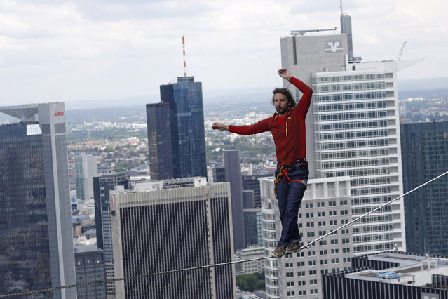 Professional slackliner Reinhard Kleindl walks a high wire in front of the Frankfurt skyline May 25, 2013. Austrian Kleindl set a world record on Saturday by walking the highest urban high line at 607 ft (185 m). (Photo by Ralph Orlowski/Reuters)