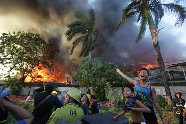 Filipino residents signal to a Philippine Air Force helicopter who helps in battling the blaze at a residential area in Mandaluyong, east of Manila, Philippines on Wednesday, November 25, 2015. Mandaluyong City Fire Marshall Nahum Tarroza said about 1,000 homes were burned during the fire. The cause of the fire is still being investigated. (Photo by Aaron Favila/AP Photo)