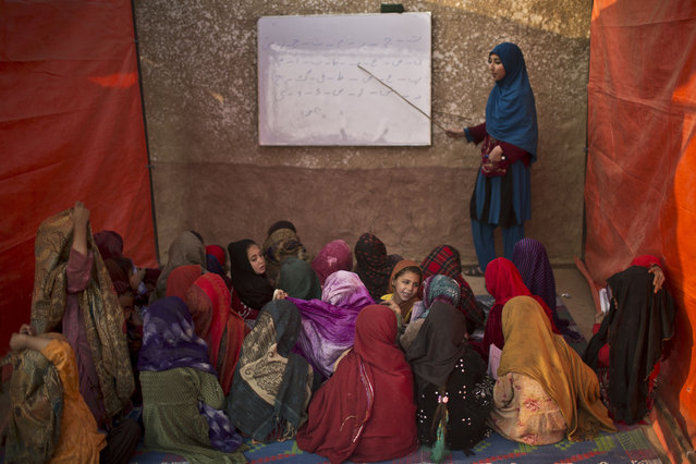 Afghan refugee girls sit on the ground attend a class to learn how to read and write the alphabet at a makeshift school in the outskirts of Islamabad, Pakistan, Monday, December 29, 2014. (Photo by Muhammed Muheisen/AP Photo)