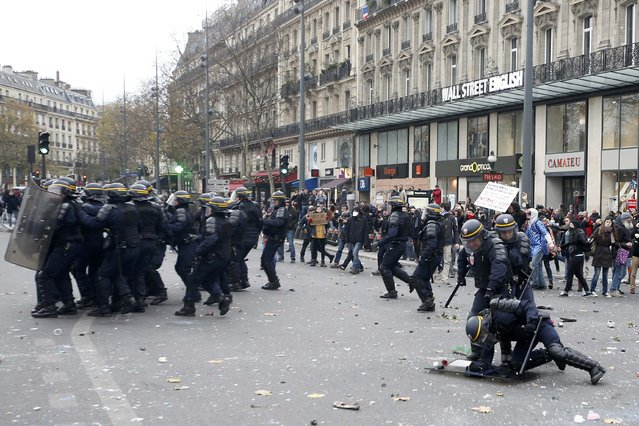 French CRS riot police take cover behind shields during clashes with demonstratores near the Place de la Republique after the cancellation of a planned climate march following shootings in the French capital, ahead of the World Climate Change Conference 2015 (COP21), in Paris, France, November 29, 2015. (Photo by Eric Gaillard/Reuters)